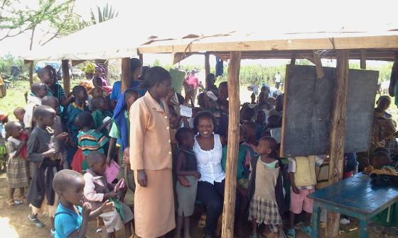 Irene (in white) sits with several children at Manjani Mingi in the shed that now serves as their school. Construction on a new school is currently underway.